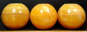 Orange Calcite Tea Light Candle Holder in the shape of a ball or sphere